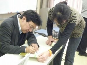 本にサインをする田中さん